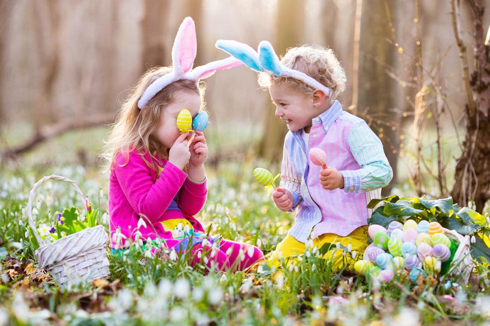 Children on Easter egg hunt in blooming spring garden